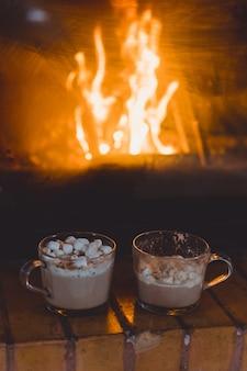 Canecas de cacau com marshmallows perto da lareira.