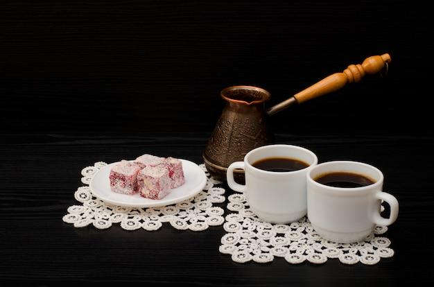 Canecas de café, delícias turcas e vasos de cerejeira em um fundo preto