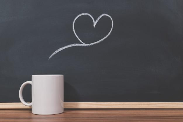 Canecas de café e formas de coração na lousa
