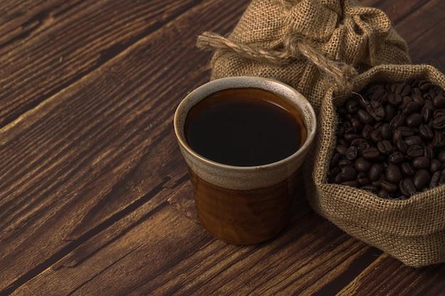 Canecas de café e grãos de café na mesa de madeira