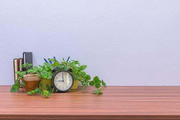 Canecas de café, relógios e plantas estão à sua mesa.