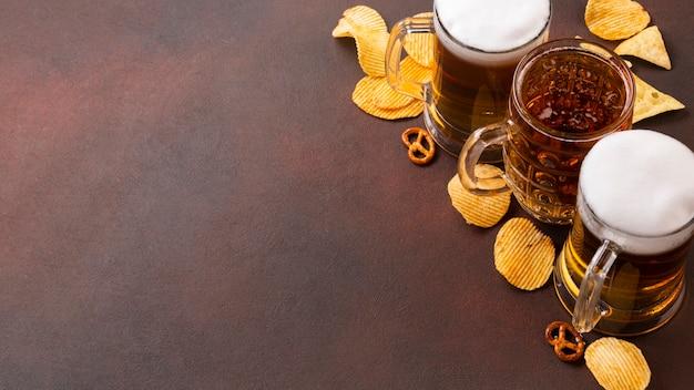 Canecas de cerveja com espuma e lanches