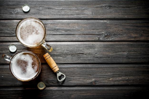 Canecas de cerveja e abridor. em fundo de madeira