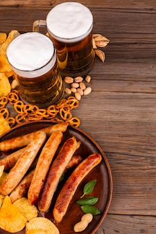 Canecas de cerveja e prato com salsichas