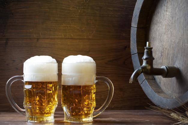 Canecas de cerveja grandes ao lado do barril de madeira