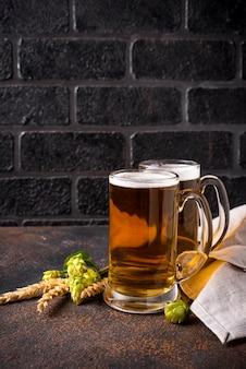 Canecas de cerveja, lúpulo e malte