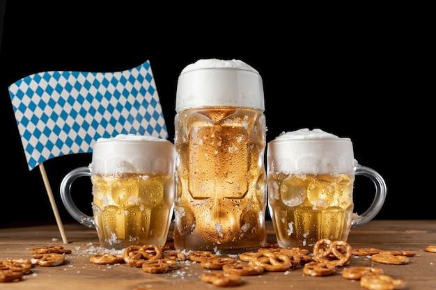 Canecas de cerveja oktoberfest com lanches em uma tabela