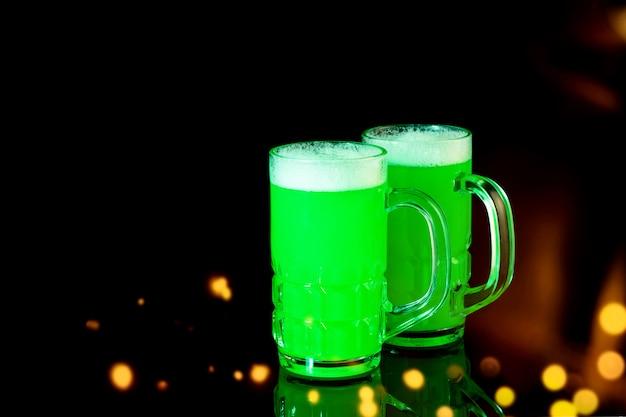 Canecas de cerveja verde para comemorar o dia de são patrício no preto