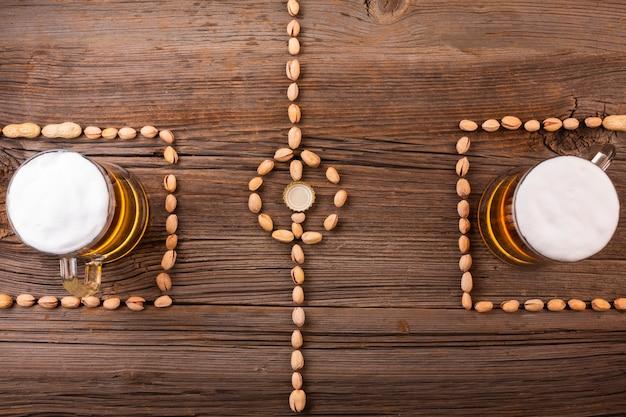 Canecas de cerveja vista superior com fundo de madeira