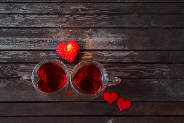 Canecas de chá em forma de coração com chá vermelho e coração vermelho