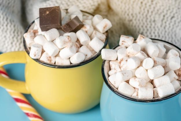 Canecas de chocolate quente com marshmallows em cima e fure um pirulito.