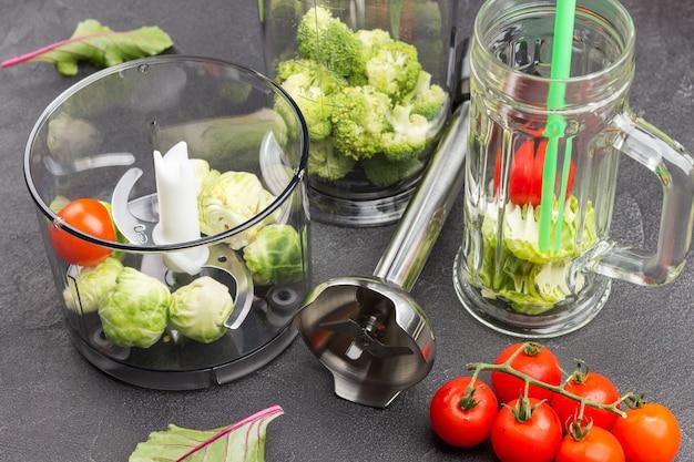 Canecas de vidro com brócolis e canudos verdes. tomates e folhas de acelga,