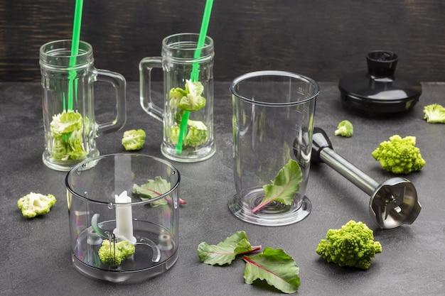 Canecas de vidro com folhas de brócolis e canudos verdes.