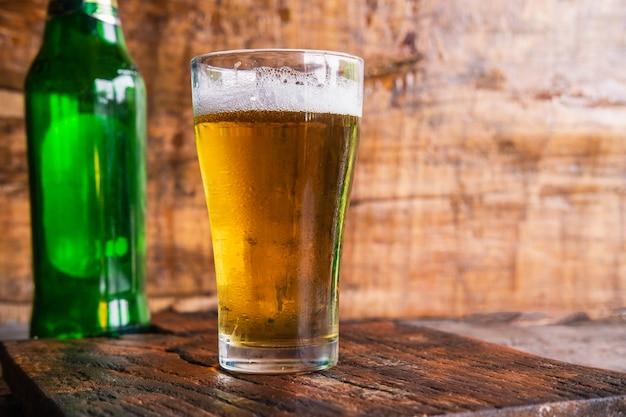 Canecas e garrafas de cerveja em uma mesa de madeira