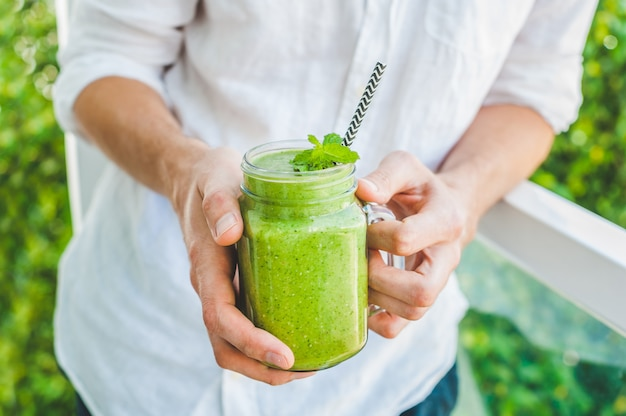 Canecas em frasco de vidro com espinafre verde, banana e vitamina de leite de coco com uma colher de aveia