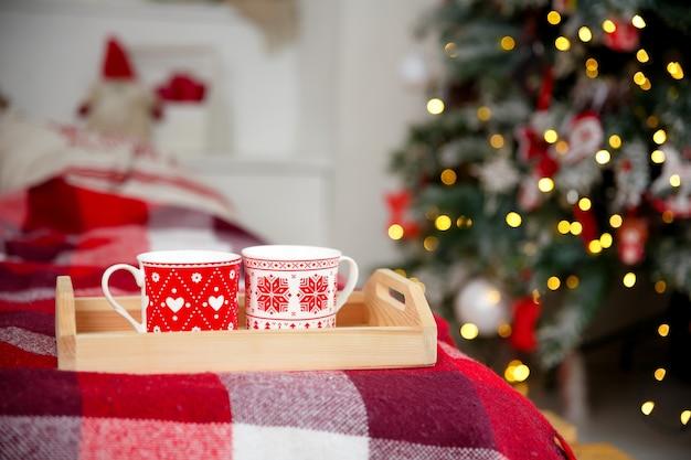 Canecas vermelhas e brancas, em uma bandeja de madeira perto da árvore do ano novo.