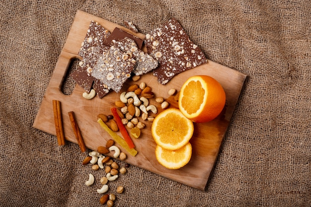 Canela e nozes alaranjadas do chocolate na mesa de madeira.