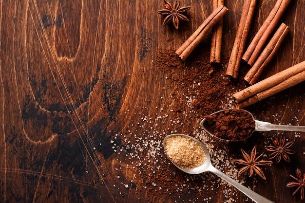 Canela natural variada, açúcar mascavo de cana, café moído, estrelas de anis assando ingredientes em uma mesa marrom rústica.
