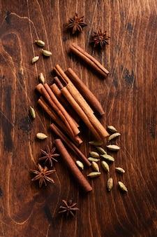 Canela natural variada, cardamomos e estrelas de anis assando ingredientes em uma mesa marrom rústica.