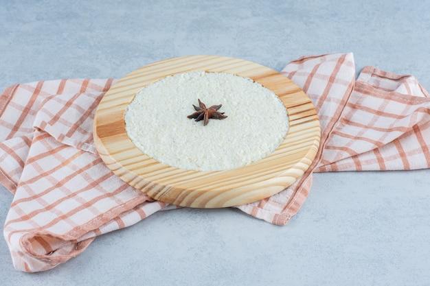 Canela no mingau de aveia na placa de madeira na toalha no mármore.