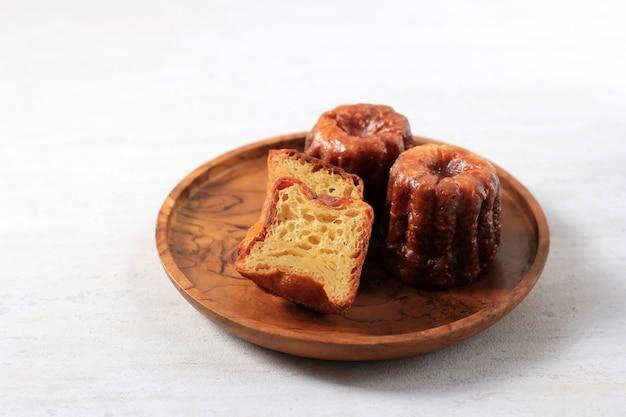 Canele ou cannele, pastelaria francesa de bordéus. sabores de rum e baunilha com centro de creme macio e crosta grossa caramelizada. servido em prato de madeira isolado no fundo branco, foco seletivo