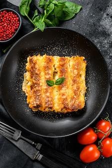 Canelone com molho de carne e tomate. massa caseira italiana. fundo preto. vista do topo