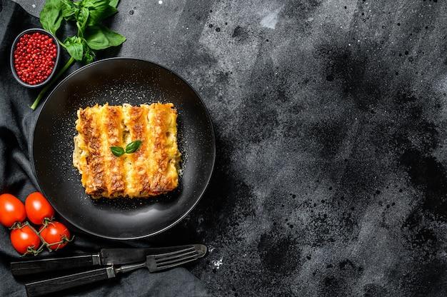 Canelone de massa caseiro italiano com molho de carne e tomate. fundo preto. vista do topo. copie o espaço