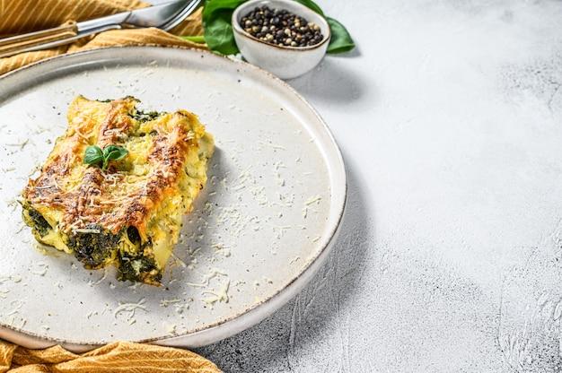 Canelone de massa vegetariana recheada assada com brócolis, espinafre, manjericão e queijo. fundo cinza. vista do topo. copie o espaço