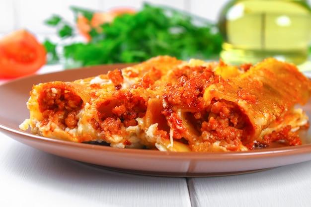 Canelone italiano tradicional da massa. tubos assados recheados com carne picada com queijo parmesão