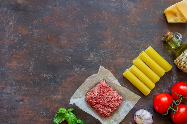 Canelone, tomate, carne picada e outros ingredientes. fundo escuro. cozinha italiana.
