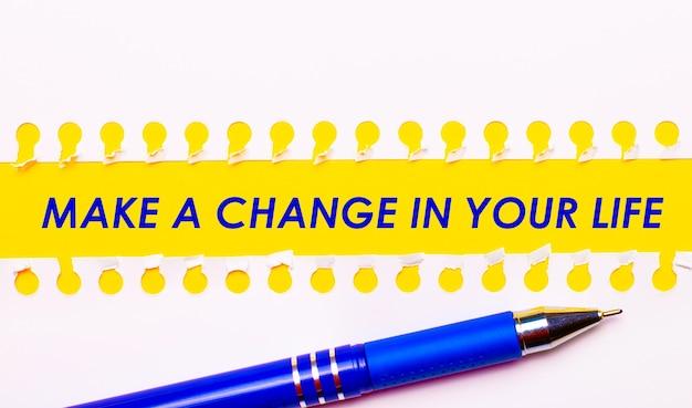 Caneta azul e listras brancas de papel rasgado em um fundo amarelo brilhante com o texto faça uma mudança em sua vida