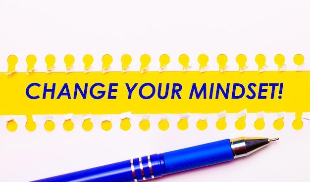 Caneta azul e listras brancas de papel rasgado em um fundo amarelo brilhante com o texto mude sua mentalidade