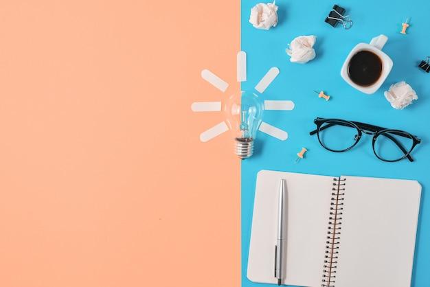 Caneta, bloco de notas, óculos, lâmpada em fundo laranja e azul.