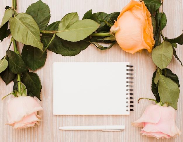 Caneta branca e bloco de notas em branco espiral rodeado com rosas sobre fundo de madeira