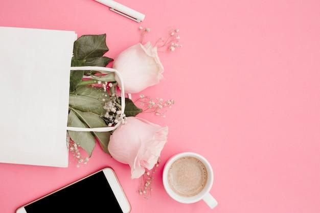 Caneta branca; rosas na sacola de compras; copo de smartphone e café em fundo rosa
