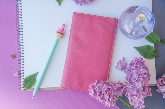 Caneta, carteira e frasco de perfume com flores diferentes