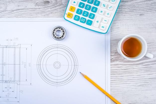 Caneta, chá e calculadora na mesa de papel com diagrama