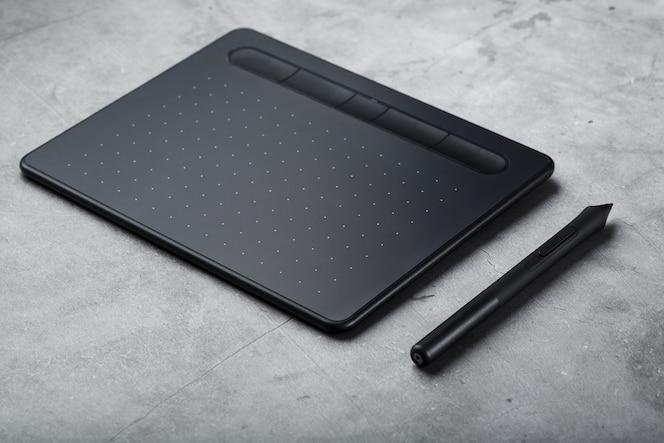 Caneta com um tablet gráfico nas mãos do designer, close-up. gadget para arte e trabalho.