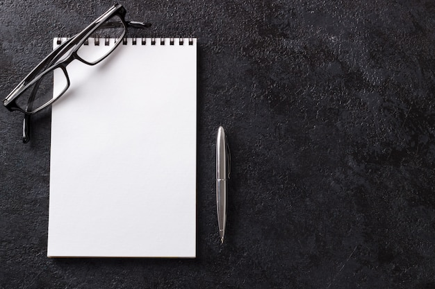 Caneta de bloco de notas em branco e óculos na mesa de escritório moderna de madeira escura mock up vista superior