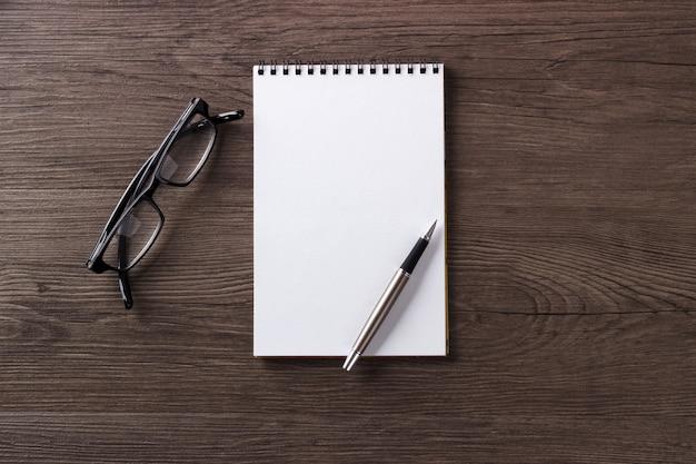 Caneta de bloco de notas em branco e óculos