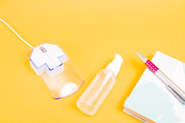 Caneta de bloco de notas para mouse de computador e anti-séptico de álcool em gel em uma superfície amarela