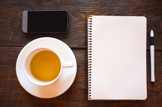 Caneta de bloco de notas para telefone e xícara de chá
