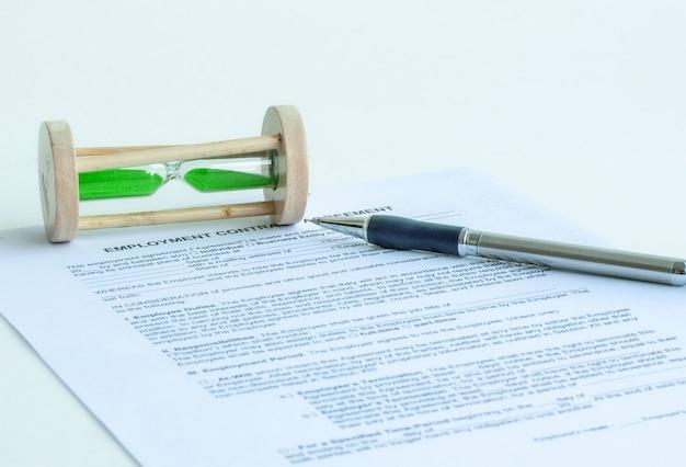 Caneta de cor azul e ampulheta em documento de formulário isolado no fundo branco com traçado de recorte. pronto para usar.