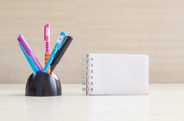 Caneta de cor closeup com mesa de cerâmica preta arrumada para caneta e página branca no livro de nota