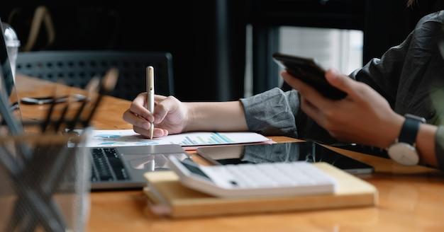 Caneta de empresário apontando rotatividade com relatório de gráfico gráfico e uso de computador portátil para análise de dados.