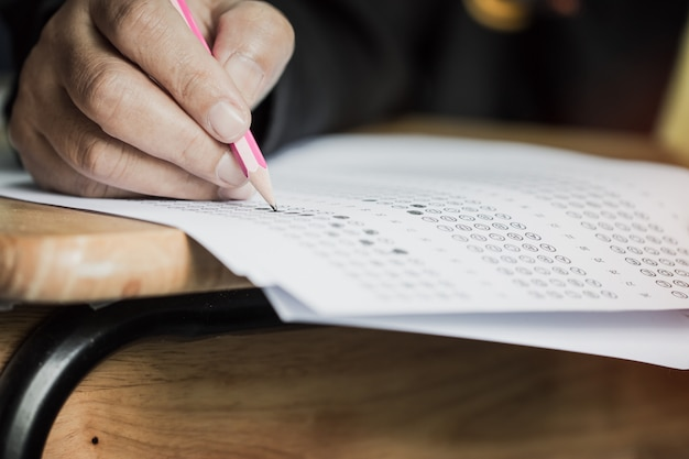 Caneta de exploração de estudante de mãos para exames de teste escrevendo folha de respostas ou exercício para tomar preenchimento