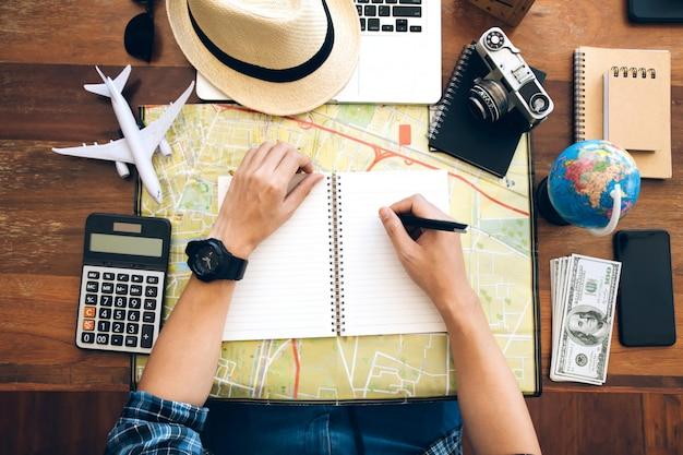 Caneta de exploração de mão masculino no caderno sobre o mapa. planejando uma viagem, copie o espaço. fundo de viagens