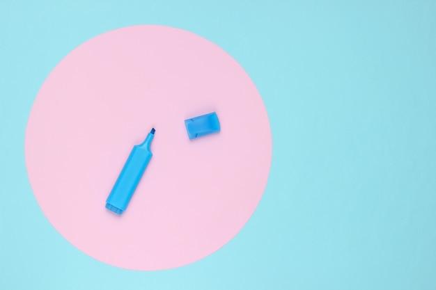 Caneta de feltro sobre fundo azul com círculo rosa pastel. vista do topo.