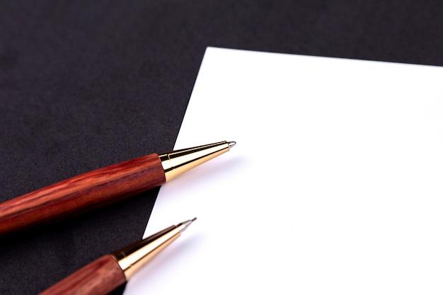 Caneta de luxo e lapiseira em madeira e ouro com uma folha branca de papel