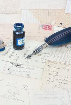 Caneta de pena azul em papéis velhos e fundo de carta